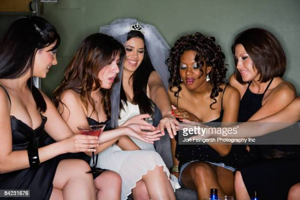 Friends admiring woman's engagement ring in nightclub