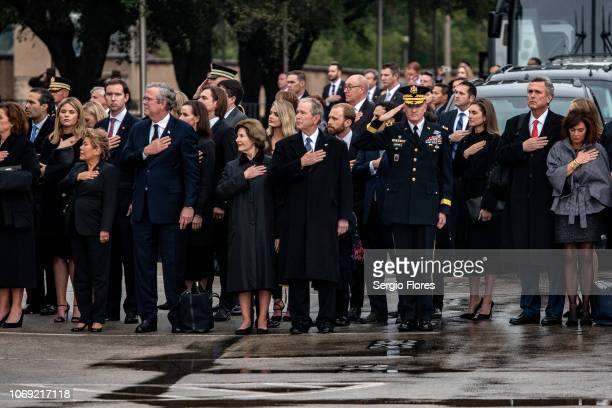 Friends and Bush family members salute and hold their hands over their hearts as they wait for the casket of former President George H.W. Bush on...