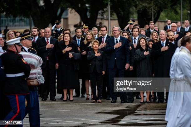 Friends and Bush family members salute and hold their hands over their hearts as they watch the casket of former President George H.W. Bush on...