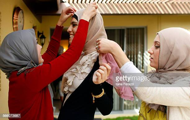 Friends and business partners Nora Diab left and Marwa Atik adjust a new hijab on friend Marwa Biltagi in the backyard of Atik's home Atik and Diab...