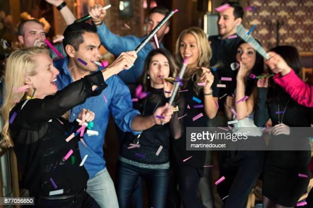 """vrienden en collega's vieren met confettis in een bar. - """"martine doucet"""" or martinedoucet stockfoto's en -beelden"""
