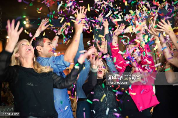 friends and coworkers celebrating with confettis  in a bar. - work party stock pictures, royalty-free photos & images