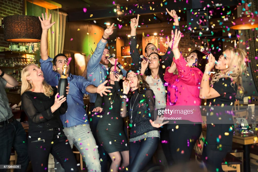 Friends and coworkers celebrating with confettis  in a bar. : Stock Photo