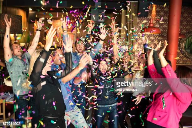 vrienden en collega's vieren met confettis in een bar. - vreugde stockfoto's en -beelden