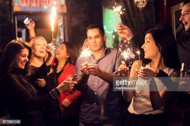 Vänner och medarbetare firar med tomtebloss i en bar.