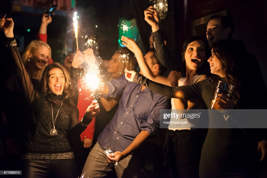 Friends and coworkers celebrating with sparklers in a bar. : Stock Photo