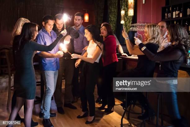 Vänner och arbetskamrater belysning tomtebloss firar i en bar.
