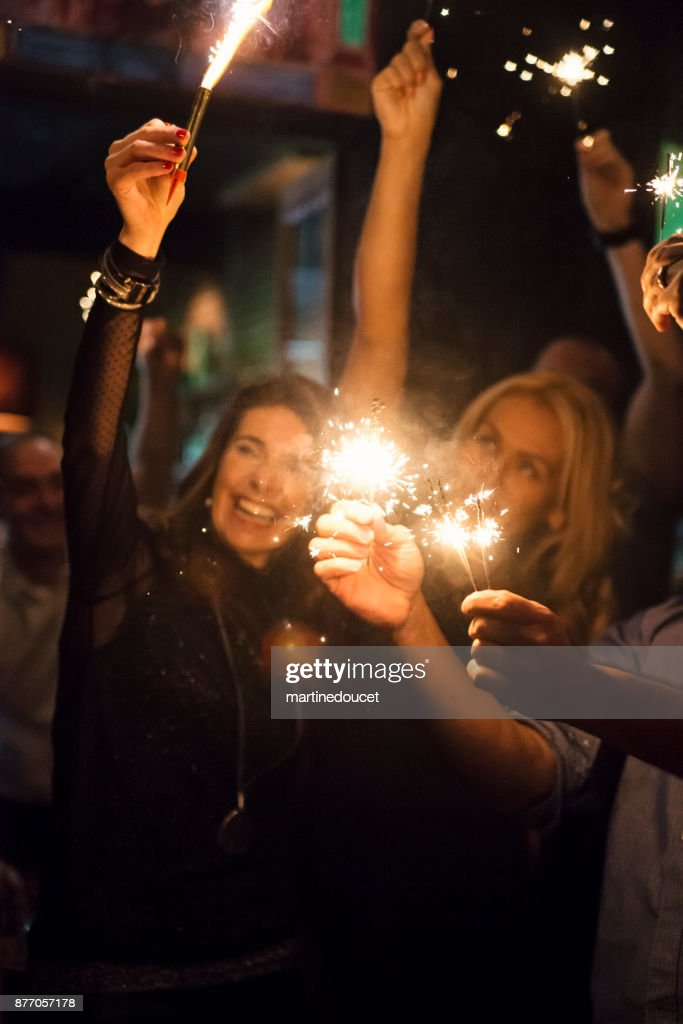 Friends and coworkers lighting sparklers celebrating in a bar. : Stock Photo