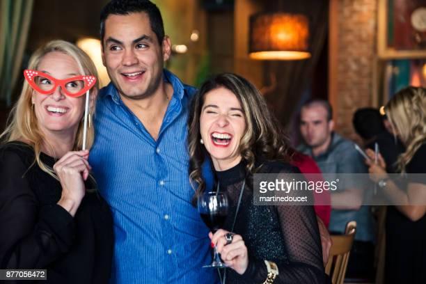 """vrienden en collega's photo booth op een partij in een bar. - """"martine doucet"""" or martinedoucet stockfoto's en -beelden"""
