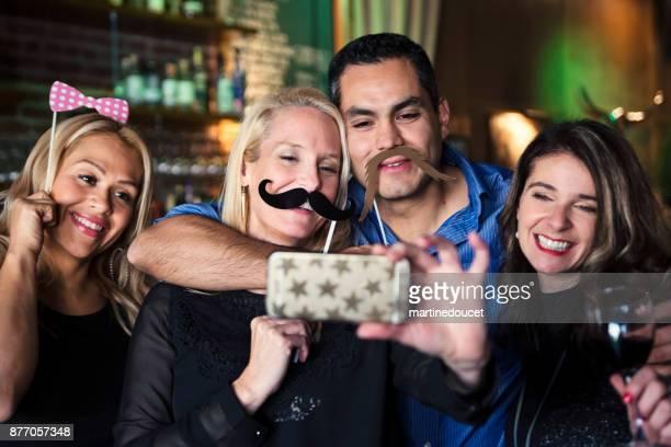 """amigos y compañeros de trabajo foto booth en una fiesta en un bar. - """"martine doucet"""" or martinedoucet fotografías e imágenes de stock"""