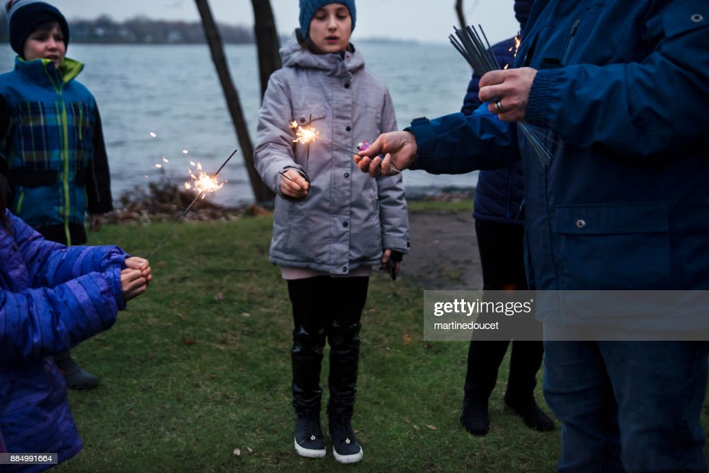 Friends and family celebrating winter with sparklers outdoors at dusk : Stock Photo