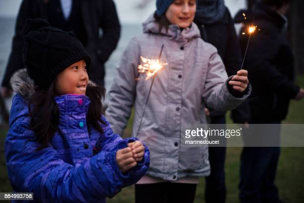 Friends and family celebrating winter with sparklers outdoors at dusk