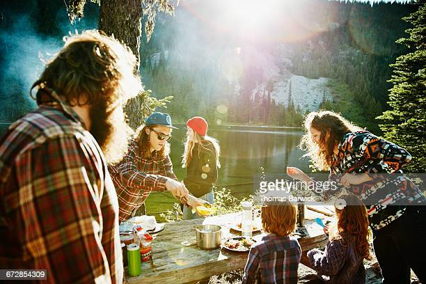 Friends and family dishing up dinner while camping
