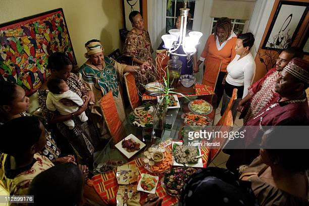 Friends and family join hands to share Kwanzaa blessings before eating special dishes prepared by Maisie McNaught at her home in Miami Gardens...