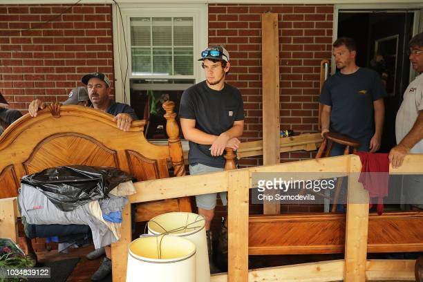 Friends and family members, including Jake Turner , works to salvage belongings from George Skinner's home, damaged by floodwaters from the Nuese...