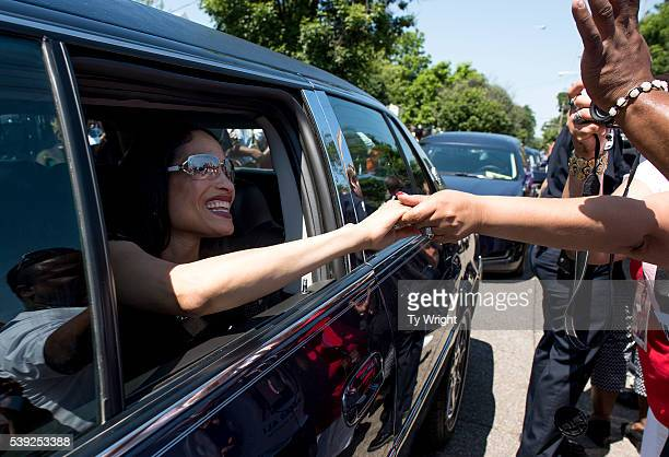 Friends and family of Muhammad Ali shake hands with people in the crowd lining Grand Avenue as the funeral procession motorcade drives in front Ali's...