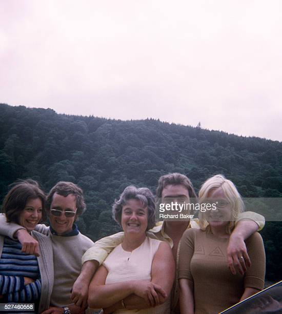 Friends and family portrait with Welsh hills in the background in the 1970s With an evergreen forest behind them we see two couples accompanied by...