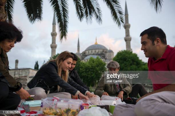 friends and family ready to eat ramadan iftar meal in istanbul, turkey - iftar stock pictures, royalty-free photos & images