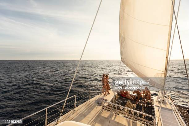 friends and family relaxing on boat deck at sunset - catamaran stock photos and pictures