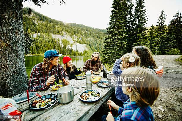 Friends and family sharing a meal while camping