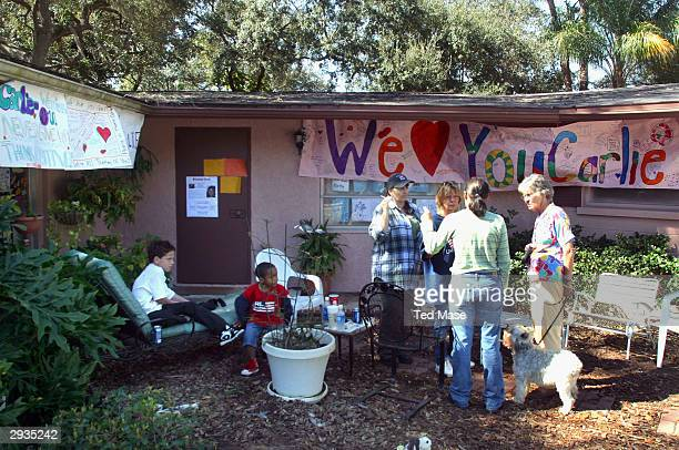 Friends and family stand outside of Carlie Brucia's house February 5 2004 in Sarasota Florida Authorities are holding Joseph P Smith in connection...