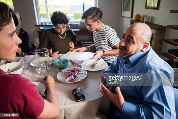 friends and family talking at dining table in dinner party - fugitive stock photos and pictures