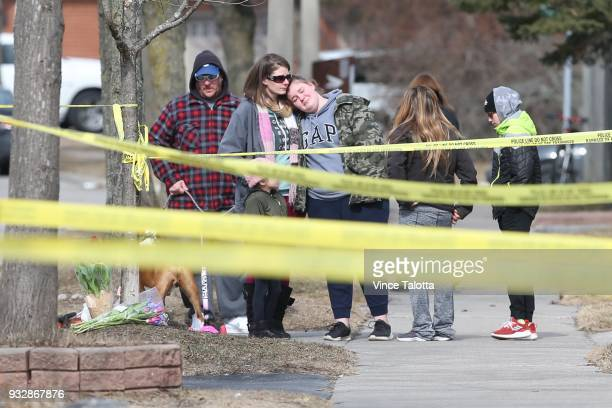 Friends and nearby residents Jennifer and her daughter Kyla Sampson and other family members lay flowers near the home where a 39yearold woman and...
