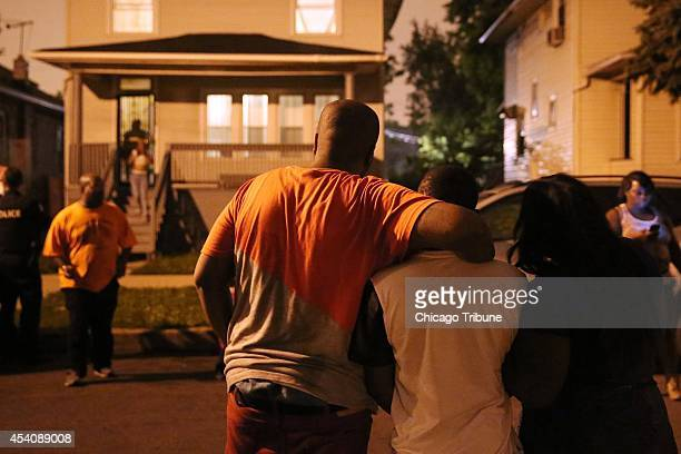 Friends and relatives grieve near the scene where three people were shot including a 33yearold man who died in the early morning hours on Sunday Aug...