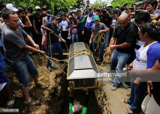 Friends and relatives help to bury the coffin containing the body of the student Gerald Velazquez shot dead during clashes with riot police in a...