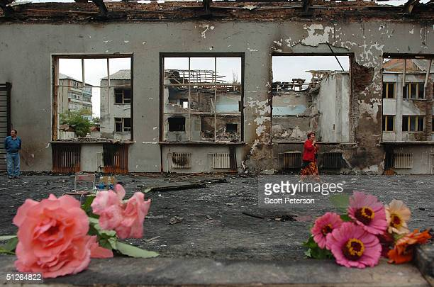 Friends and relatives left flowers at the ruins of the destroyed school where more than 350 people were killed during a hostage situation on...