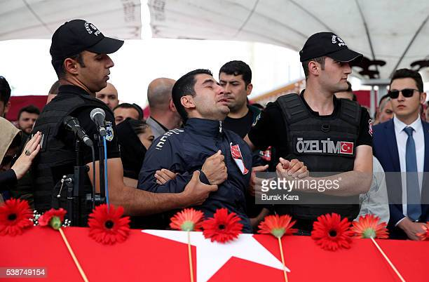 Friends and relatives mourn during the funeral of Turkish police officers Gokhan Topcu and Kadir Cihan Karagozlu who were among seven Turkish police...