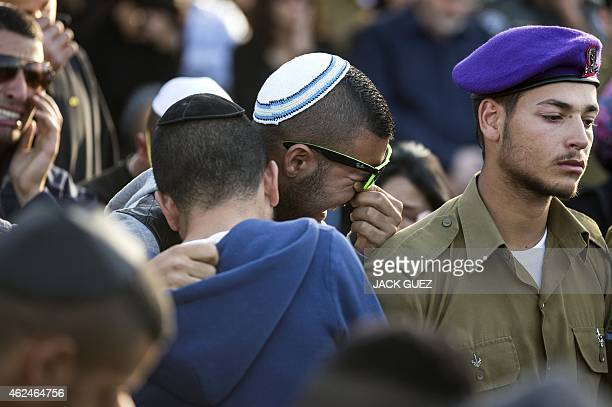 Friends and relatives of 20yearold Israeli Staff Sergeant Dor Chaim Nini mourn during his funeral in a cemetery in the town of Shtulim east of the...