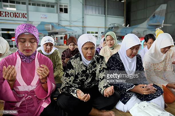 Friends and relatives of passengers and crew members from the missing Adam Air flight take part in a group prayer at Hasanuddin Airport in Makassar,...