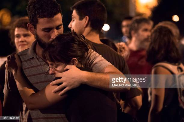 Friends and relatives of the Brazilian politician Marielle Franco react as they await the Rio's Civil Police procedures at Marielle's car where she...