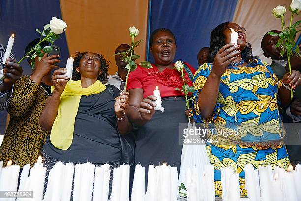 Friends and relatives of victims hold candles as they pray and sing on April 7, 2015 in Nairobi, on the final day of mourning for the 148 people...