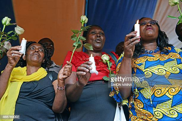 Friends and relatives of victims hold candles as they pray and sing on April 7 2015 in Nairobi on the final day of mourning for the 148 people killed...