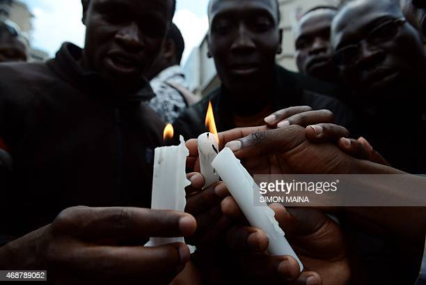 Friends and relatives of victims light candles during a gathering on April 7 2015 in Nairobi on the final day of mourning for the 148 people killed...