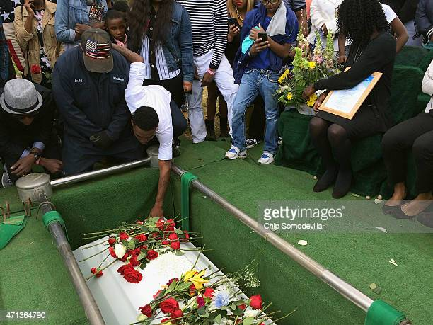 Friends and relatives say their last goodbyes to Freddie Gray as his casket is lowered into his grave at the Woodland Cemetery April 27 2015 in...