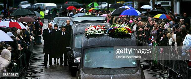 Friends and relatives walk behind the funeral cortege for footballer George Best as it makes its way from the private service held at his family home...
