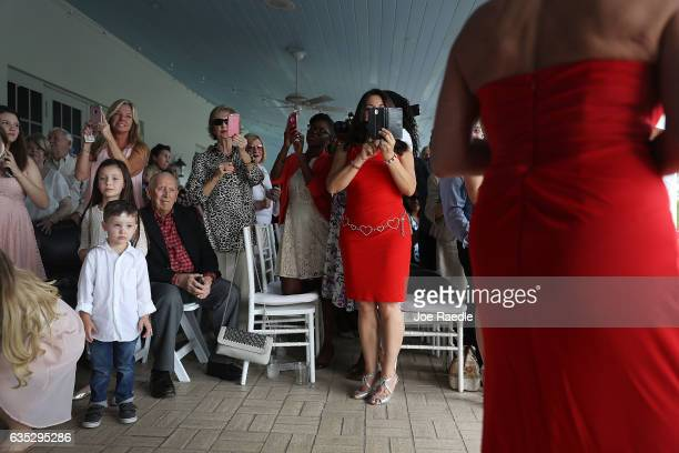 Friends and relatives watch as loved ones arrive to participate in a group Valentine's day wedding ceremony at the National Croquet Center on...