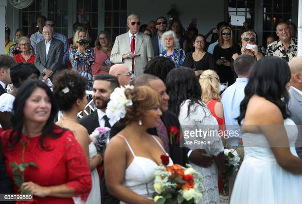 Friends and relatives watch as loved ones participate in a group Valentine's day wedding ceremony at the National Croquet Center on February 14 2017...