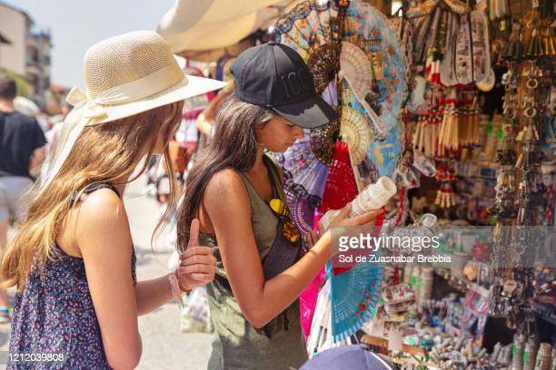 friends and sisters sightseeing in pisa, italy, buying souvenirs in a roamana store - souvenir stock pictures, royalty-free photos & images