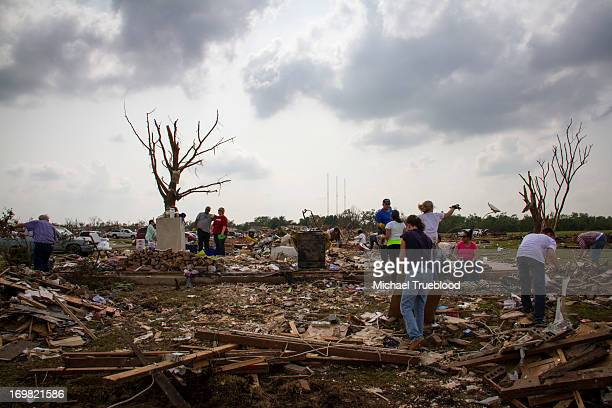CONTENT] Friends and Volunteers help the family of Nathan Kriesel go through what is left of their home in Moore Oklahoma after being hit by a...