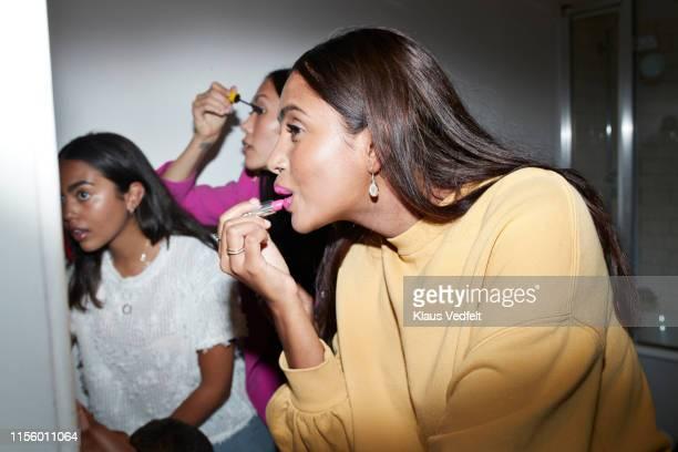 friends applying make-up together at home - pintalabios rosa fotografías e imágenes de stock