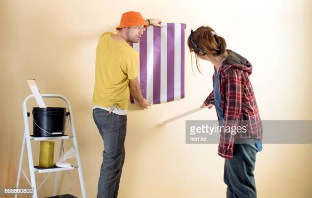 Friends applying wallpaper to wall