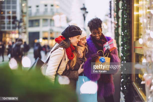 friends are buying christmas presents - feriado imagens e fotografias de stock