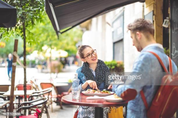 友人は、歩道のカフェで昼食します。 - オープンカフェ ストックフォトと画像