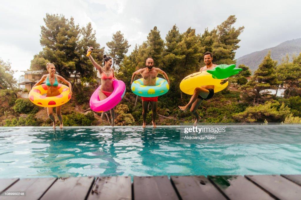 Vrienden zijn springen in het zwembad : Stockfoto