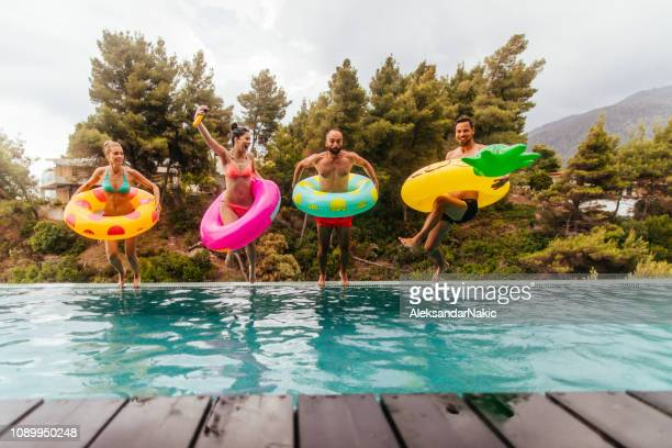 friends are jumping into the pool - pool stock pictures, royalty-free photos & images