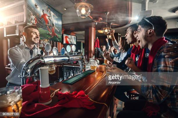 Friends are watching the soccer match and drinking beer on the bar
